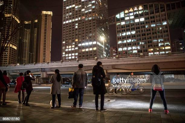Commuters wait for buses as a cyclist on a bike share passes by on March 27 2017 in Beijing China The popularity of bike shares has exploded in the...