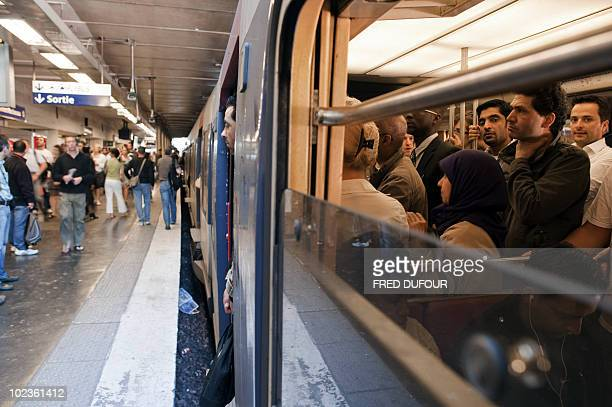 Commuters wait for the departure of a RER regional train at the DenfertRochereau station in Paris on June 24 2010 as a mass strike against the French...