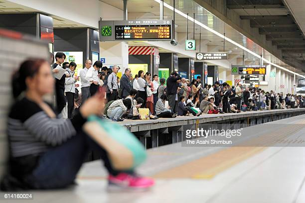 Commuters wait for the Seibu Ikebukuro Lilne service restart as the blackout continues at Ikebukuro Station on October 12 2016 in Tokyo Japan A fire...