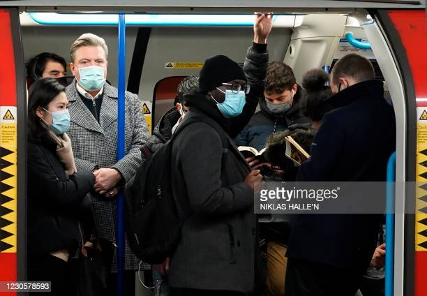 Commuters wait for their train to depart from Victoria station on the London underground in London on January 14, 2021 during Britain's third...