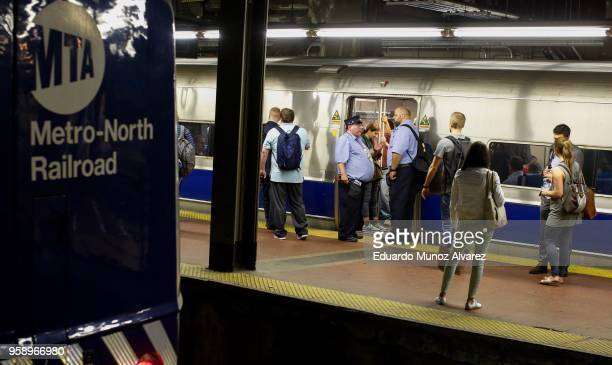 Commuters wait for train service to be restored after a severe thunderstorm downed trees that caused power outages resulting in several MetroNorth...