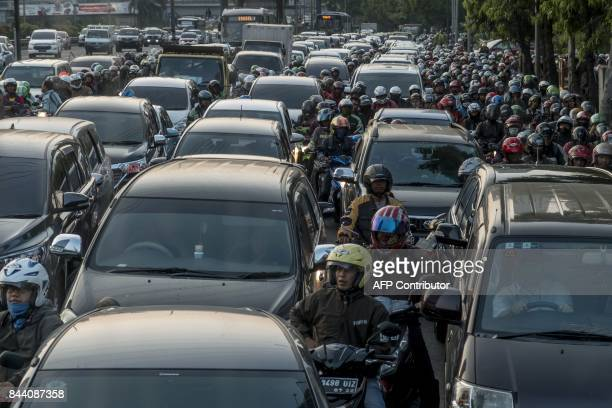 Commuters wait in a traffic jam during afternoon rush hour in Jakarta on September 8 2017 / AFP PHOTO / BAY ISMOYO