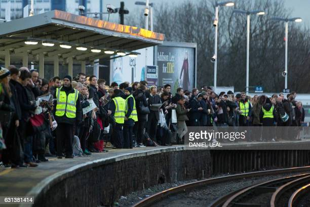 Commuters wait on a platform to catch a train toward central London at Clapham Junction station on January 10 2017 after strike action by Southern...