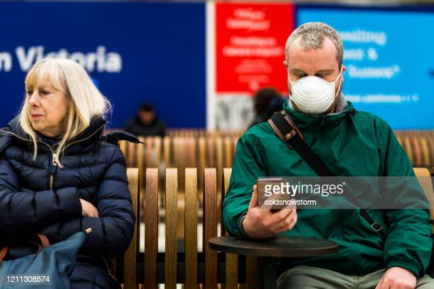 commuters waiting for train and wearing protective face mask in city railway station - railway station stock pictures, royalty-free photos & images