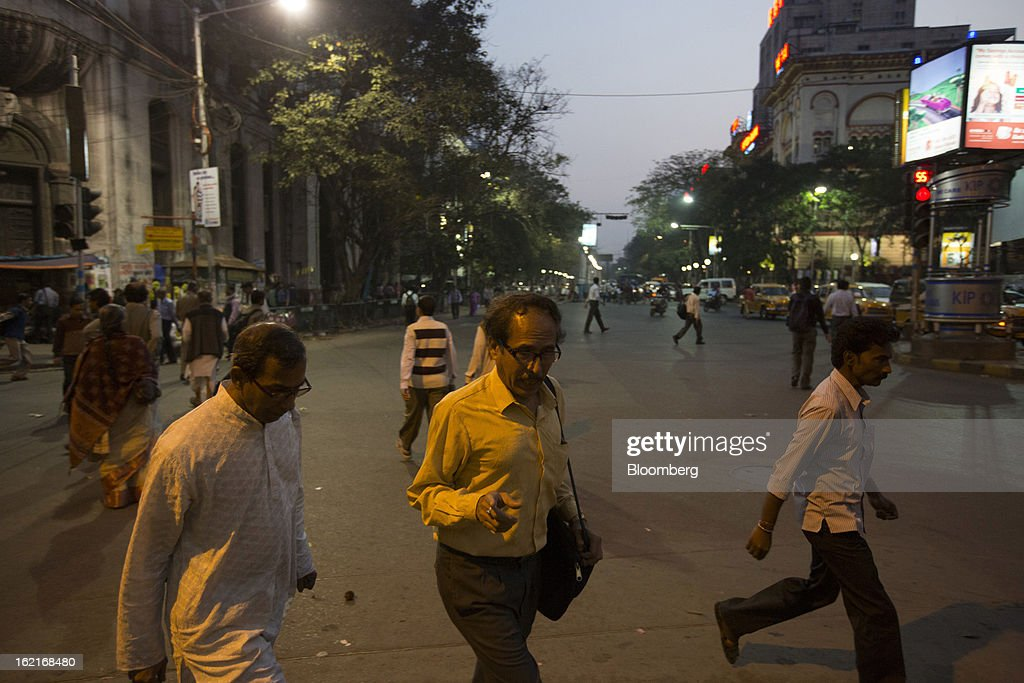 Commuters walk across a street in the evening in Kolkata, India, on Tuesday, Feb. 19, 2013. India's slowest economic expansion in a decade is limiting profit growth at the biggest companies even as foreigners remain net buyers of the nation's stocks, according to Kotak Institutional Equities. Photographer: Brent Lewin/Bloomberg via Getty Images