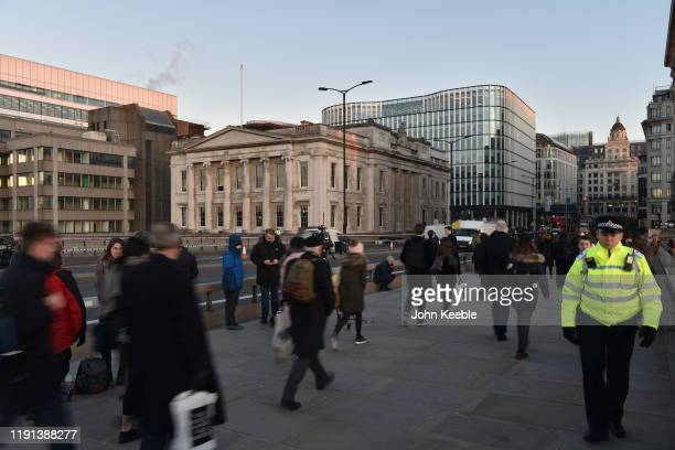 Commuters walk across London Bridge and past Fishmongers' Hall early morning as the bridge is reopened after the recent stabbing attack on December...