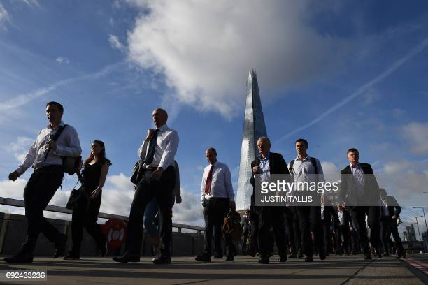 TOPSHOT Commuters walk across London Bridge backdropped by The Shard in London on June 5 after it was partially reopened following the June 3 terror...