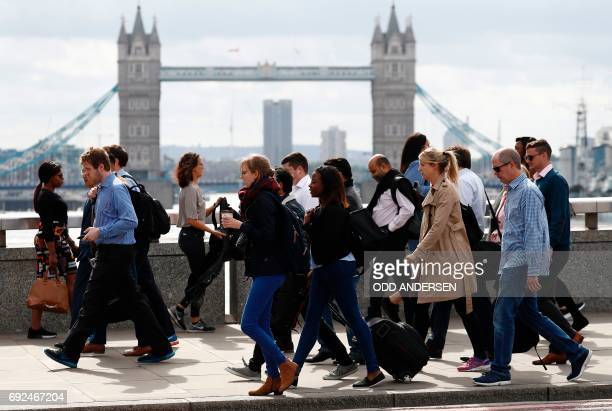 Commuters walk across London Bridge in London on June 5 after it was partially reopened following the June 3 terror attack British police on Monday...