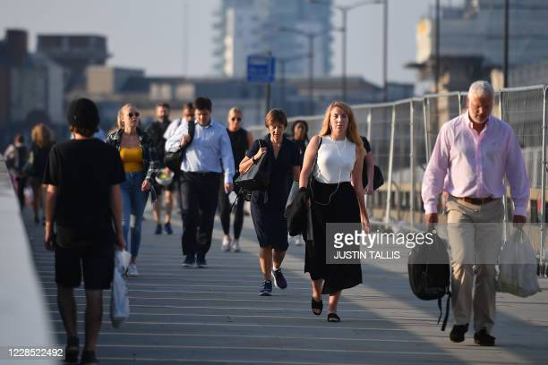 Commuters walk across London Bridge toward the City of London on September 15, 2020. - Britain's unemployment rate jumped above four percent in July...