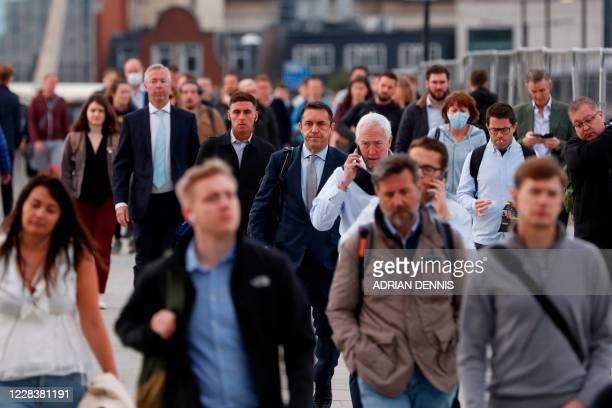 Commuters walk across London Bridge toward the City of London on September 7, 2020. - Prime Minister Boris Johnson and his Conservative government...