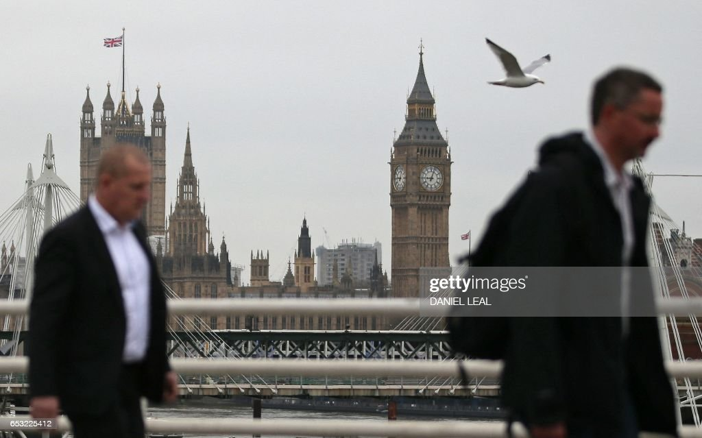 Commuters walk across Waterloo Bridge, backdropped by The Elizabeth Tower, better known as 'Big Ben', and the Houses of Parliament, in central London on March 14, 2017. Prime Minister Theresa May is set to begin the countdown to Brexit after parliament gave her the green light -- and Scotland wrong-footed her by launching a fresh bid for independence. Downing Street has played down speculation that May could announce Tuesday that she is triggering the Article 50 process to leave the European Union, indicating that it would take place later in the month. / AFP PHOTO / Daniel LEAL