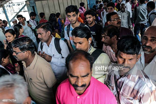 Commuters walk along a footbridge at Kurla railway station in Mumbai India on Wednesday April 15 2015 India's economic growth will power past China's...