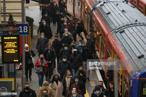 Commuters walk along a platform after arriving at London Waterloo railway station in London, U.K., on Thursday, Nov. 5, 2020. The Bank of England...