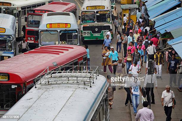 Commuters walk along a street as buses pick up and drop off passengers during the morning rush hour in Colombo Sri Lanka on Tuesday July 21 2015 The...