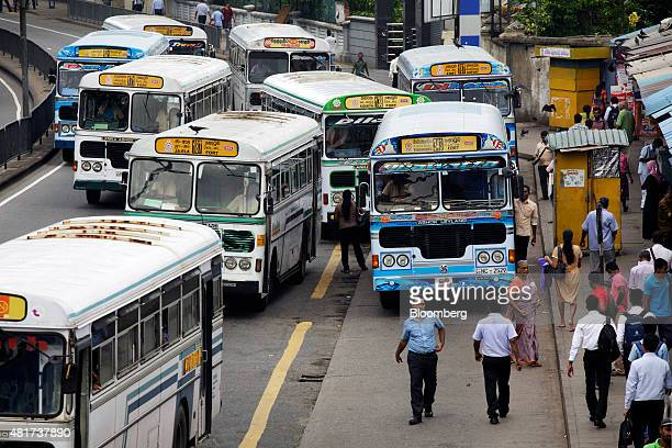 Commuters walk along a street as passengers wait for buses during the morning rush hour in Colombo Sri Lanka on Tuesday July 21 2015 The Central Bank...