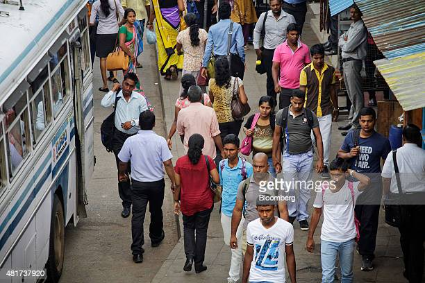 Commuters walk along a street past a bus during the morning rush hour in Colombo Sri Lanka on Tuesday July 21 2015 The Central Bank of Sri Lanka kept...
