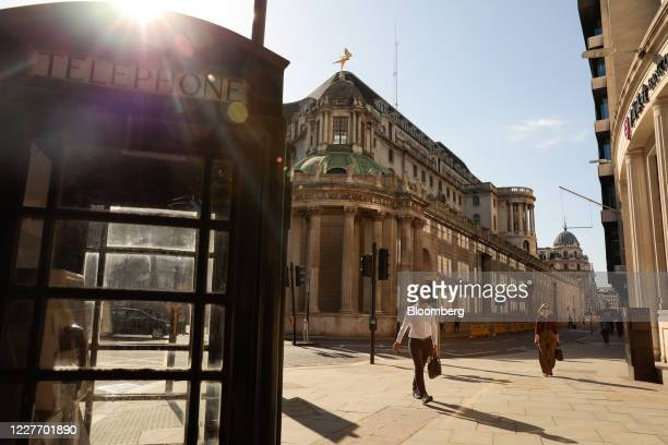 Commuters walk along a street towards a traditional red telephone box in view of the Bank of England in the City of London, U.K., on Monday, July 20,...