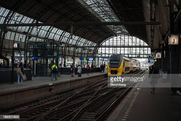 Commuters walk along platforms as a Koploper passenger train operated by Nederlandse Spoorwegen sits on the tracks at Amsterdam Centraal station in...
