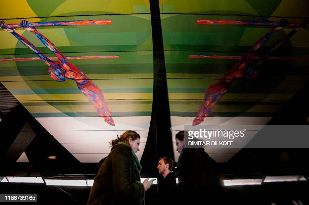 Commuters walk at CSKA /TSSKA/ metro station, with its ceiling decorated with an image of a gymnast, in Moscow on December 6, 2019. - The executive...