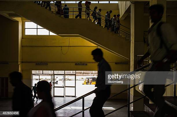 Commuters walk down a flight of stairs at the Kasturibai Nagar train station in Chennai Tamil Nadu India on Monday July 21 2014 Optimism about a...