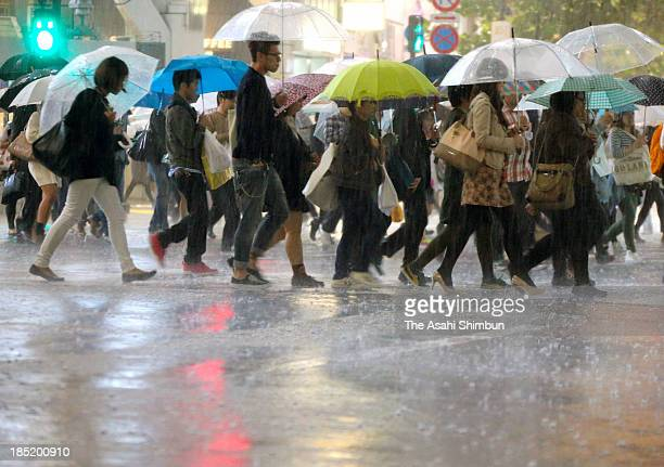 Commuters walk in the heavy rain as Typhoon Wipha approaching at Shibuya Station on October 15 2013 in Tokyo Japan