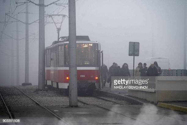 Commuters walk next to a tram in heavy smog on January 9 2018 in Sofia Bulgaria's capital Sofia was all doneup to host incoming European Union...