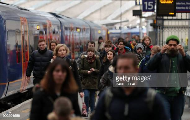 Commuters walk on the platform at Waterloo station in central London on January 2 2018 As the price of an average ticket rose by 34 percent on...