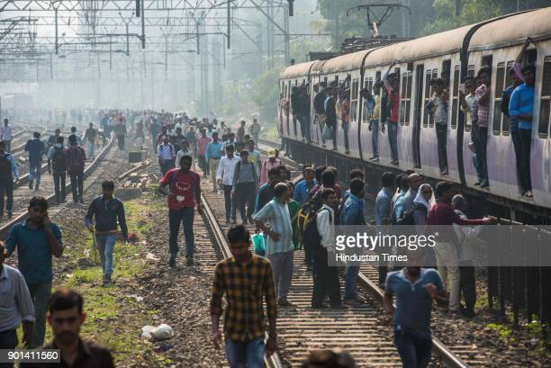 Commuters walk on the railway track during Maharashtra Bandh between Mulund and Thane as Dalit protestors protest and demand arrested of Sambhaji...