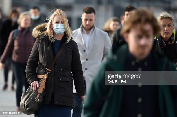 Commuters walk over London Bridge during the morning rush hour in central London on November 2, 2020. - A second national UK lockdown is set to come...