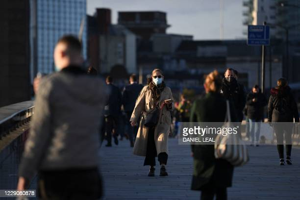 Commuters walk over London Bridge toward the City of London during the morning rush hour on October 15, 2020. - Prime Minister Boris Johnson on...