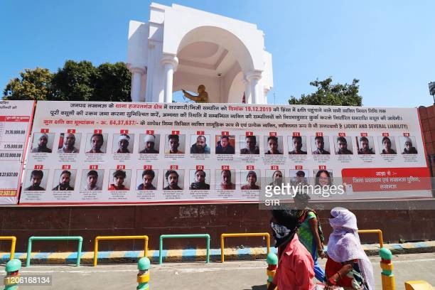 Commuters walk past a billboard installed by Uttar Pradesh authorities displaying pictures, names and addresses of people accused of vandalism during...
