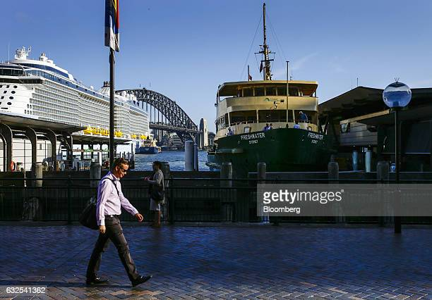 Commuters walk past a docked ferry in the Circular Quay area as Royal Caribbean Cruises Ltd's Ovation Of The Seas cruise ship left and the Sydney...