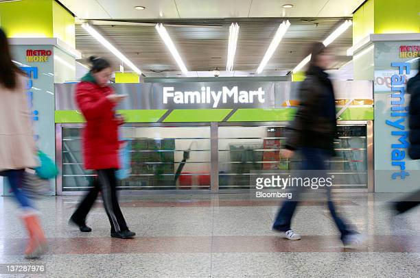 Commuters walk past a FamilyMart Co convenience store at a subway station in Shanghai China on Sunday Jan 15 2012 FamilyMart Co Japan's largest...