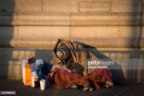 Commuters walk past a homeless man wrapped in a few blankets sleeps sitting up with his belongings as the sunrises on Tower Bridge London United...