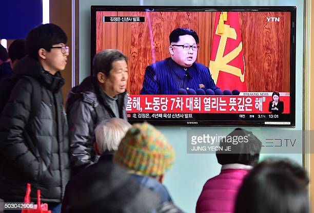 Commuters walk past a television screen showing a broadcast of North Korean leader Kim JongUn's New Year speech at a railroad station in Seoul on...