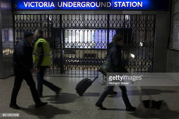 Commuters walk past closed station gates at Victoria during the 24hr tube strike affecting Londoners and passengers throughout the capital on 9th...