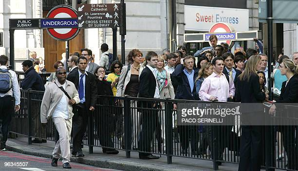Commuters walk past Monument Underground Station after subway and bus lines were closed after terrorist attacks in London 07 July 2005 Explosions...