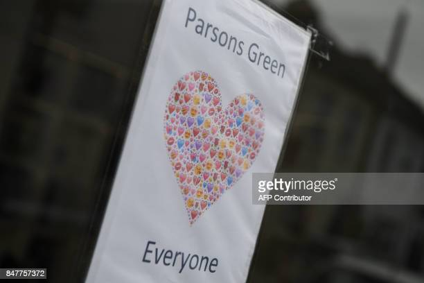 Commuters walk past proParsond Green signs posted in the window of an estate agent near Parsons Green station which was reopened in the early hours...