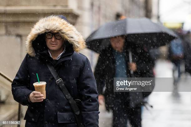 Commuters walk through a wintry mix of snow and sleet during the morning rush hour in the Financial District March 10 2017 in New York City A winter...