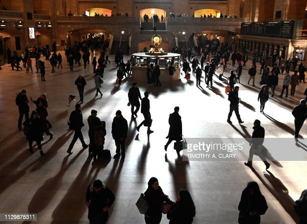Commuters walk through the morning bright sunlight coming from the 60 feet high windows in Grand Central Terminal in New York City on March 11 2019...