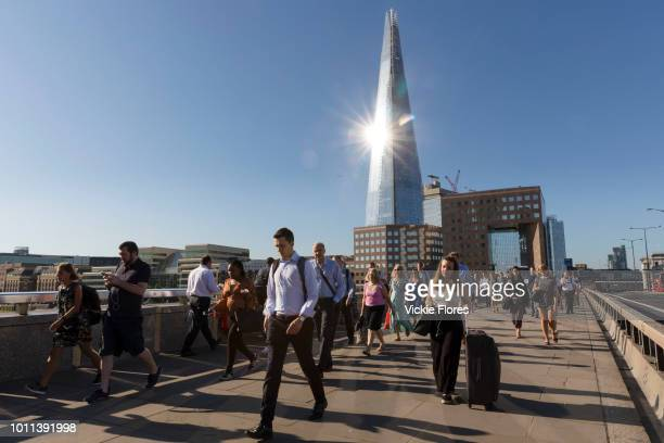 Commuters walk to work across London Bridge as the sun reflects on the London Shard in London England on August 03 2018 during hot sunny weather as...