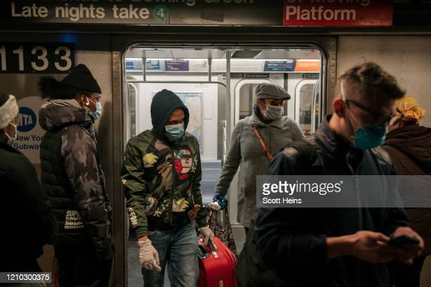 Commuters wear face masks as they exit a subway train on April 17 2020 in New York City Following a new order from Governor Andrew Cuomo that New...