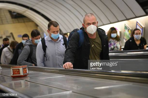 Commuters wear face masks as they pass through Vauxhall underground station on the first day of their mandatory use while travelling on public...