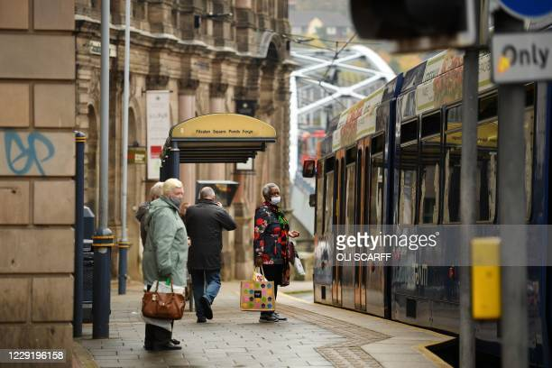 Commuters wear face masks as they wait at a tram stop in Sheffield, south Yorkshire on October 21 prior to further lockdown measures as the number of...