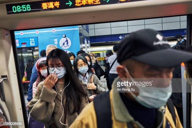 Commuters wear face masks at a railway station on December 02, 2020 in Taipei, Taiwan. Taiwan imposed mandatory mask-wearing regulations in some...