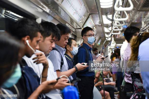 Commuters wear face masks on the Mass Rapid Transit train as a preventive measure against the COVID-19 coronavirus in Singapore on March 18, 2020.
