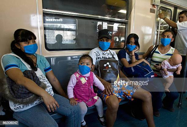 Commuters wear face masks to prevent the infection by the swine flu virus in while travelling aboard Mexico City's subway on April 24 2009 An...