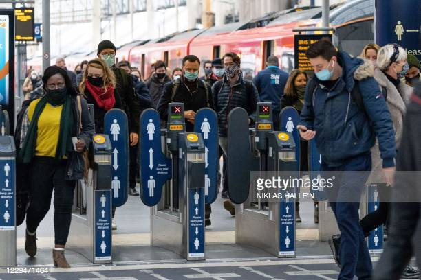 Commuters wear facemasks as they walk at Waterloo Station in central London on November 5 as England enters a second novel coronavirus COVID-19...