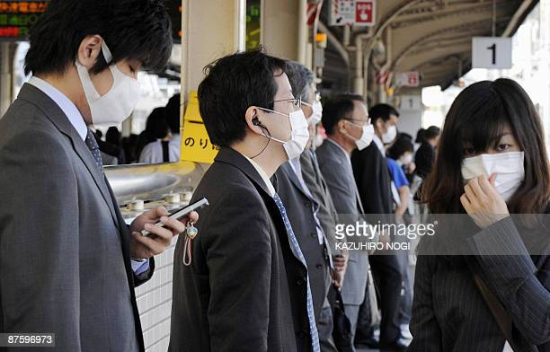 Commuters wear facemasks while waiting for a train at a railway station in Kobe, Hyogo prefecture, in western Japan on May 18, 2009. Japan shuttered...