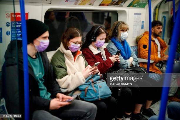 Commuters wear masks as a precaution whilst travelling on a London Underground metro train in the morning in central London on March 18 2020 as...